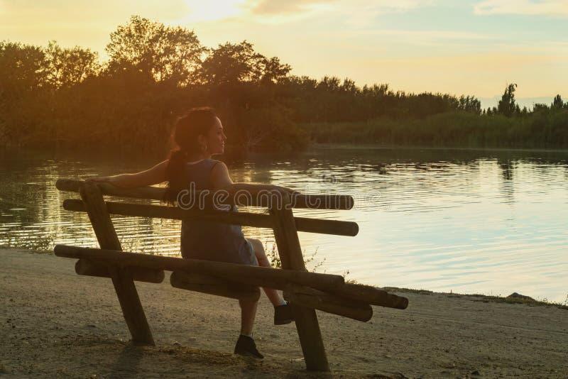 Jeune femme de brune observant le coucher du soleil photos libres de droits