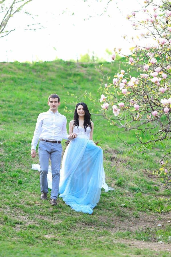 Jeune femme de brune portant la robe bleue et marchant près de la magnolia avec l'ami photographie stock libre de droits