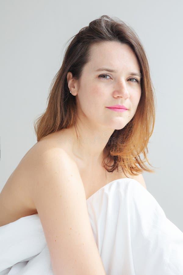 Jeune femme de brune s'asseyant dans le lit avec les draps blancs photos stock