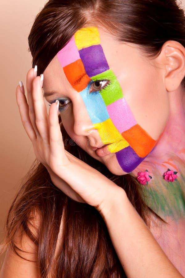 Jeune femme de brunette avec le renivellement coloré image stock