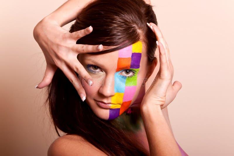 Jeune femme de brunette avec le renivellement coloré images stock