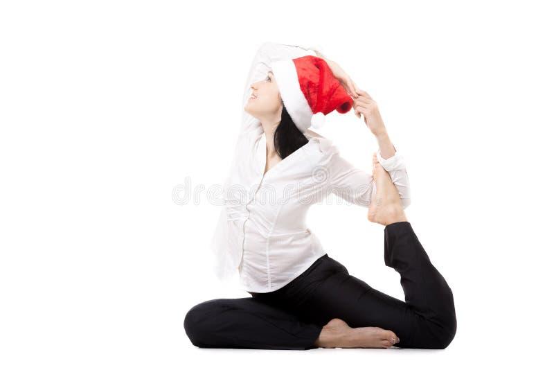 Jeune femme de bureau dans la pose de yoga de gros orteil dans le chapeau du père noël sur le wh photos stock