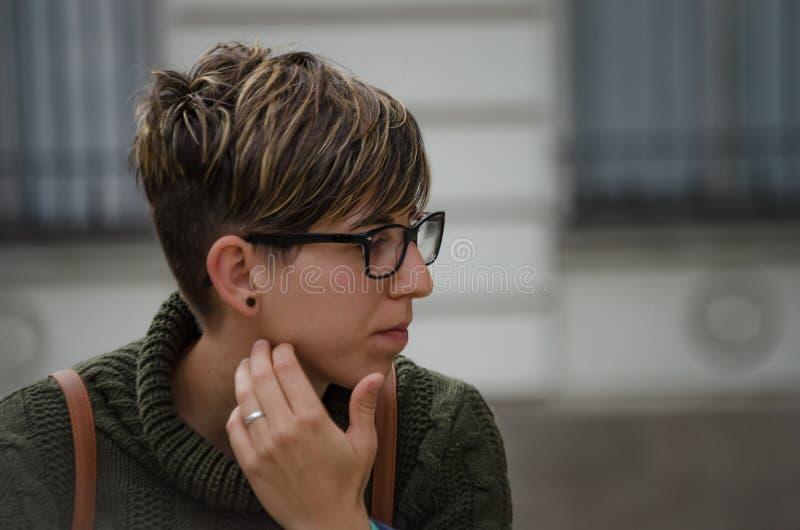 Jeune femme de caucasion avec les cheveux courts et les verres photographie stock libre de droits