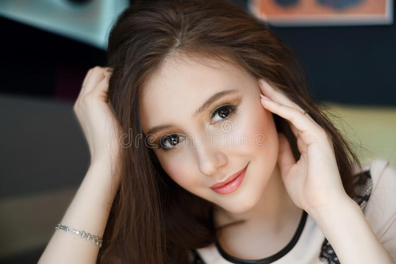 Jeune femme de charme de portrait avec le sourire amical, caf? de sourire de longs cheveux de brune photo libre de droits