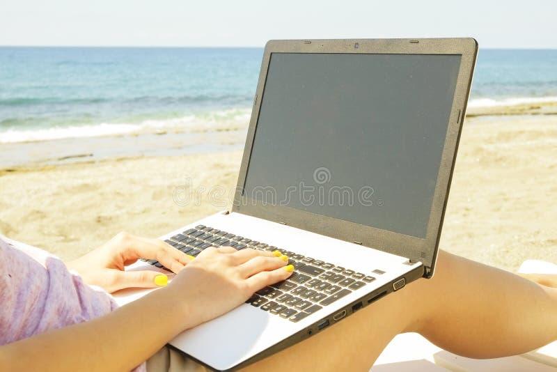 Jeune femme de cheveux blonds travaillant sur l'ordinateur portable à la plage le jour ensoleillé Fermez-vous des mains femelles  photo stock