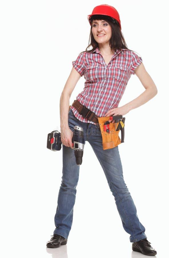 Jeune femme de constructeur avec un foret image stock