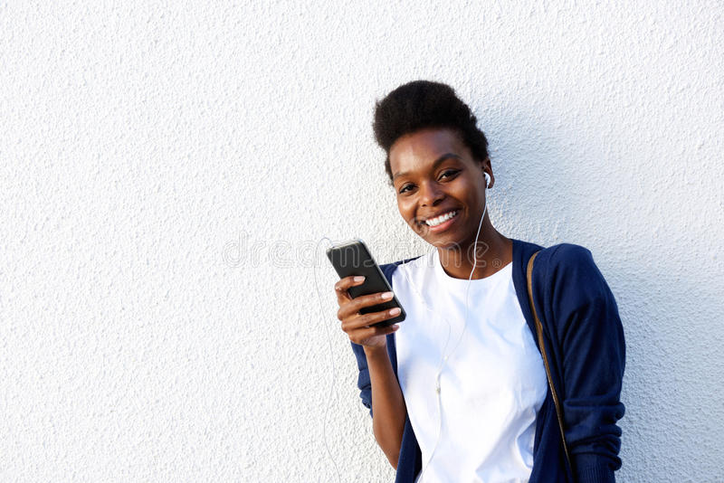 Jeune femme de couleur écoutant la musique photo stock
