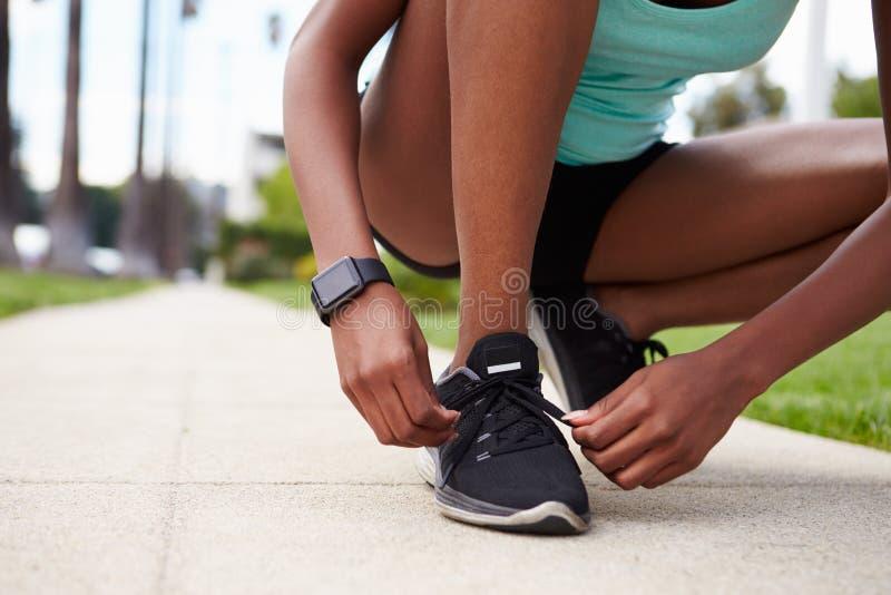 Jeune femme de couleur attachant des chaussures de sports dans la rue images stock