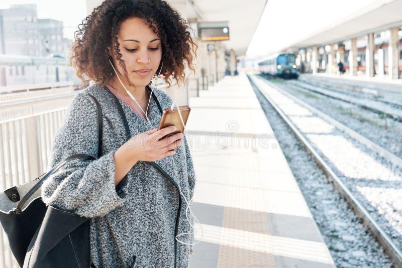 Jeune femme de couleur attendant le train photographie stock