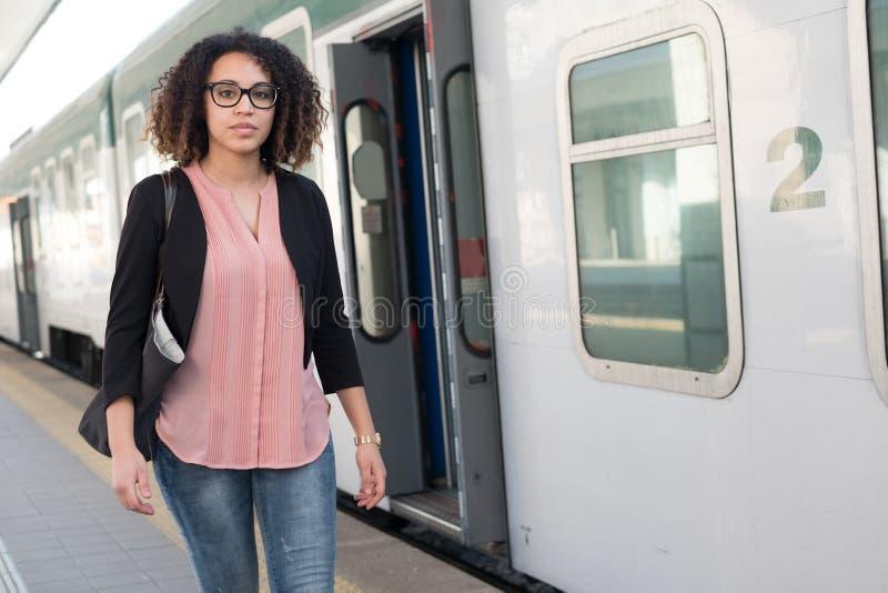 Jeune femme de couleur attendant le train image stock