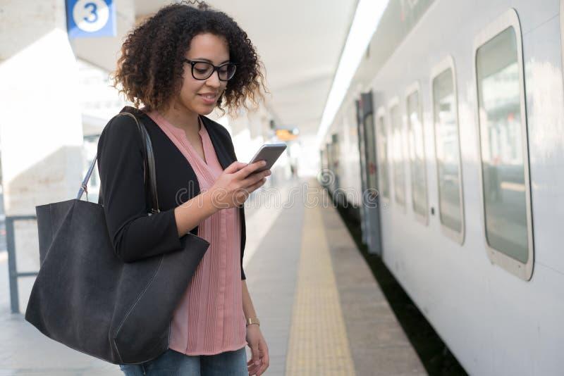 Jeune femme de couleur attendant le train photos libres de droits