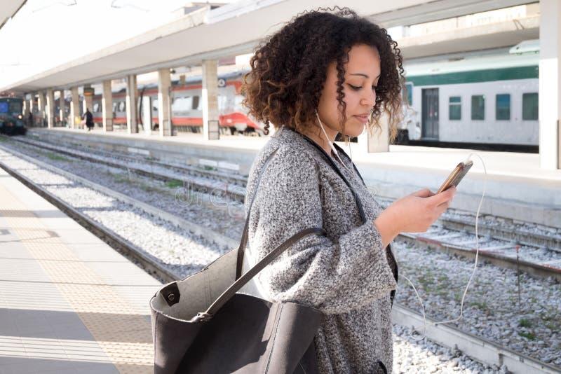 Jeune femme de couleur attendant le train images stock