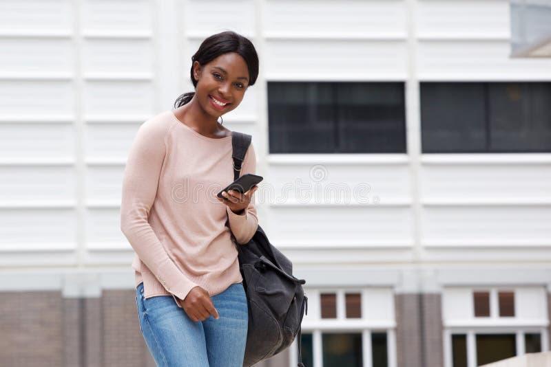 Jeune femme de couleur attirante avec le sac et téléphone portable dans la ville image libre de droits