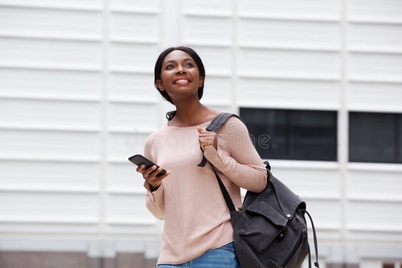 Jeune femme de couleur attirante avec le sac et téléphone portable dans la ville images stock