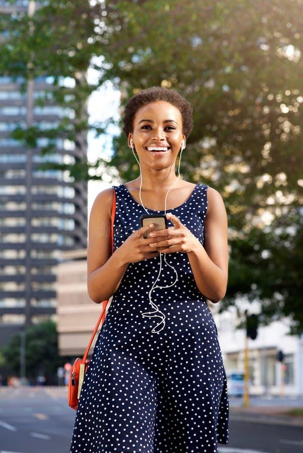Jeune femme de couleur attirante marchant dans la ville avec le mobile et les écouteurs images libres de droits