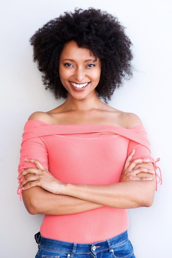 Jeune femme de couleur attirante se tenant avec des bras croisés et souriant sur le fond blanc images stock