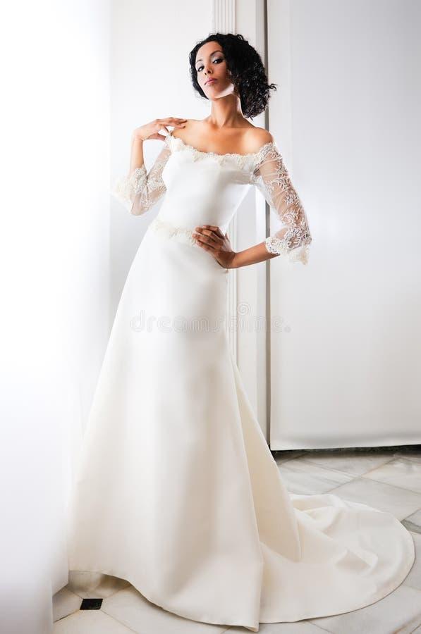 Jeune femme de couleur avec la robe de mariage photographie stock