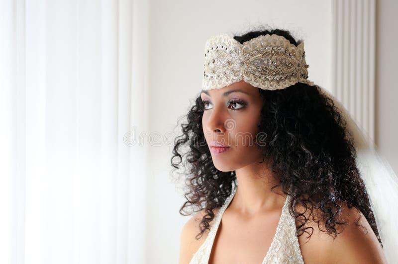 Jeune femme de couleur avec la robe de mariage image stock