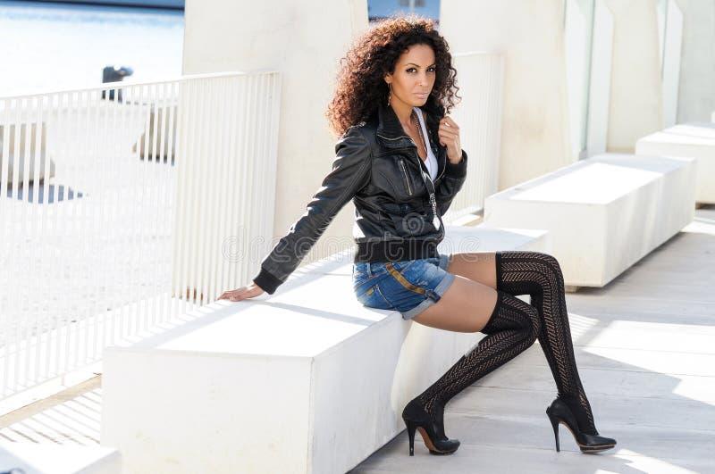 Jeune femme de couleur, coiffure Afro, à l'arrière-plan urbain image stock