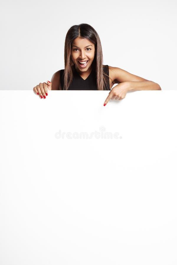 Jeune femme de couleur de sourire heureuse montrant l'enseigne vide photo stock