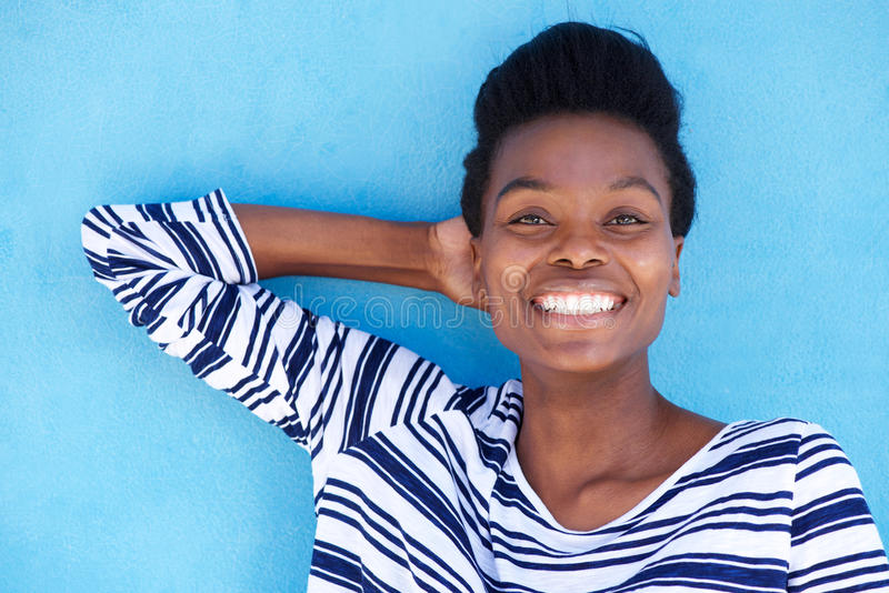 Jeune femme de couleur heureuse souriant avec la main derrière la tête images libres de droits