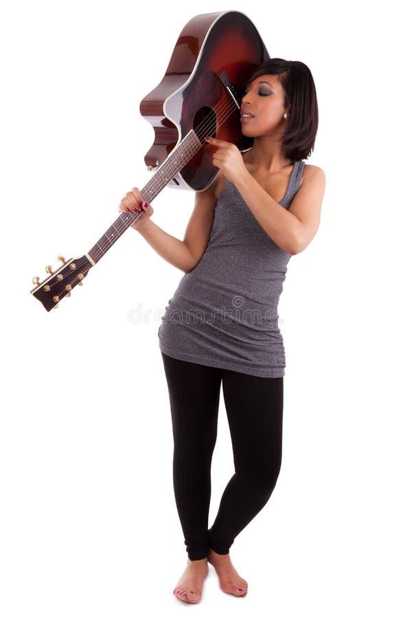 Jeune femme de couleur jouant la guitare photographie stock