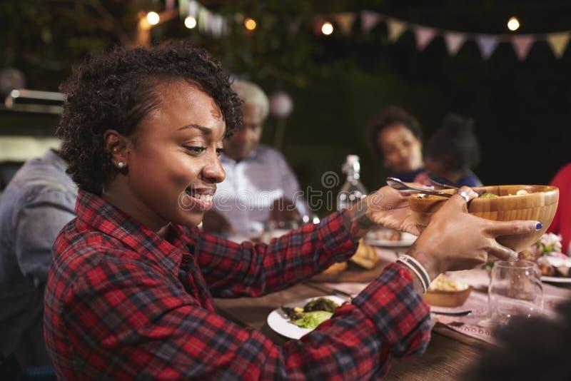 Jeune femme de couleur passant la cuvette à un barbecue de famille image libre de droits