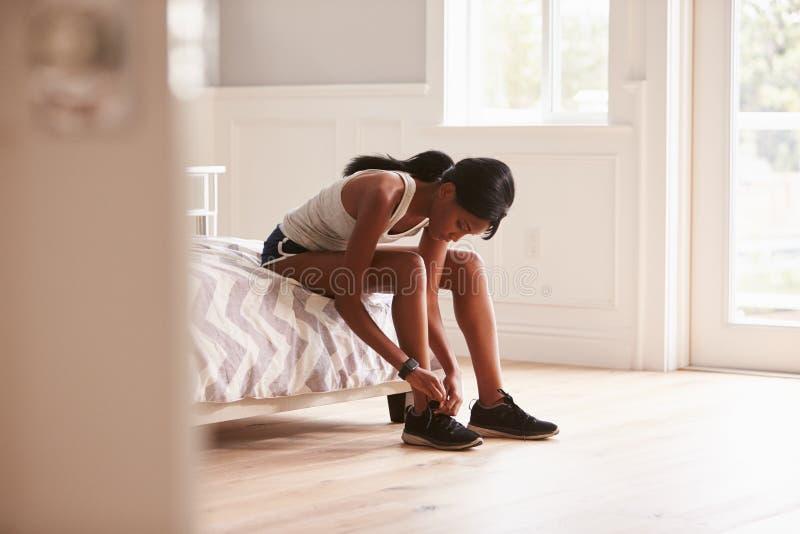 Jeune femme de couleur prête pour s'exercer attachant sa chaussure de sports image libre de droits