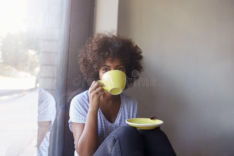 Jeune femme de couleur s'asseyant par la fenêtre en café potable de café photos stock