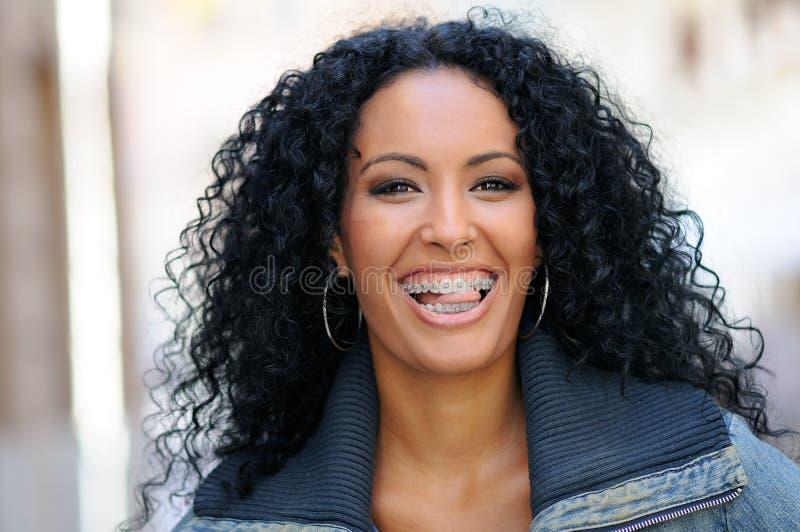 Jeune femme de couleur souriant avec des supports photo libre de droits