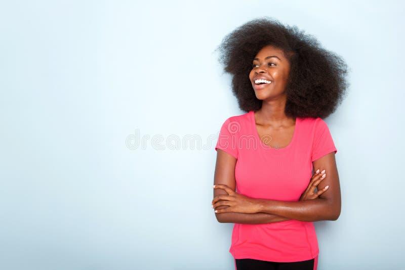 Jeune femme de couleur de sourire avec des bras croisés sur le fond bleu photographie stock libre de droits