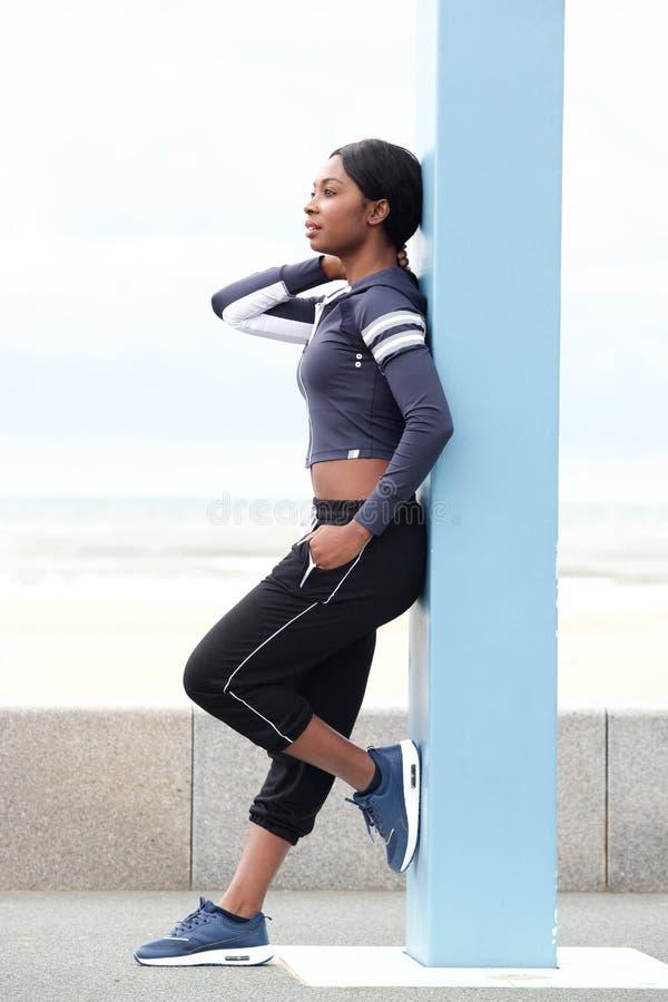 Jeune femme de couleur sportive intégrale se penchant contre le poteau dehors photos libres de droits