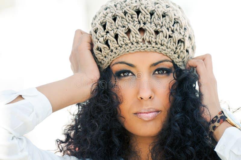 Jeune femme de couleur utilisant un capuchon de laines photo libre de droits