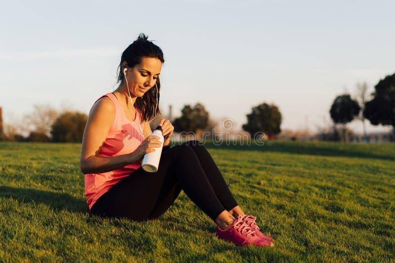 Jeune femme de coureur assise dans l'herbe avant course dans un parc, une eau potable avec le smartphone et des écouteurs Fermez- photographie stock libre de droits
