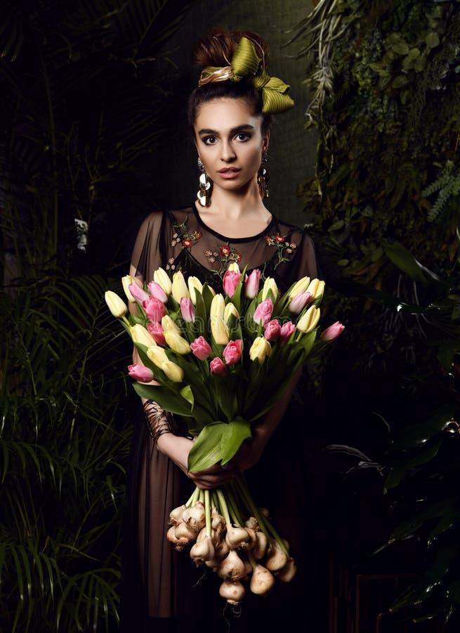 Jeune femme de cru avec le grand bouquet des fleurs blanches de tulipe de ressort frais Feuilles de vert de style de ressort photographie stock