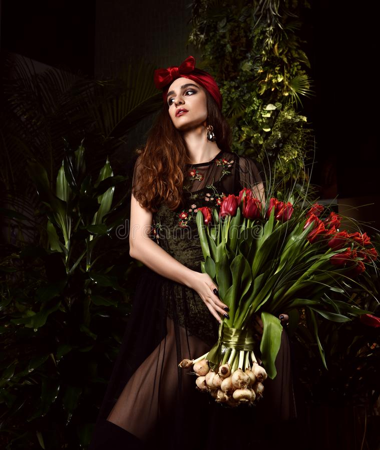 Jeune femme de cru avec le grand bouquet des fleurs rouges de tulipe de ressort frais avec des ampoules Feuilles de vert de style images stock