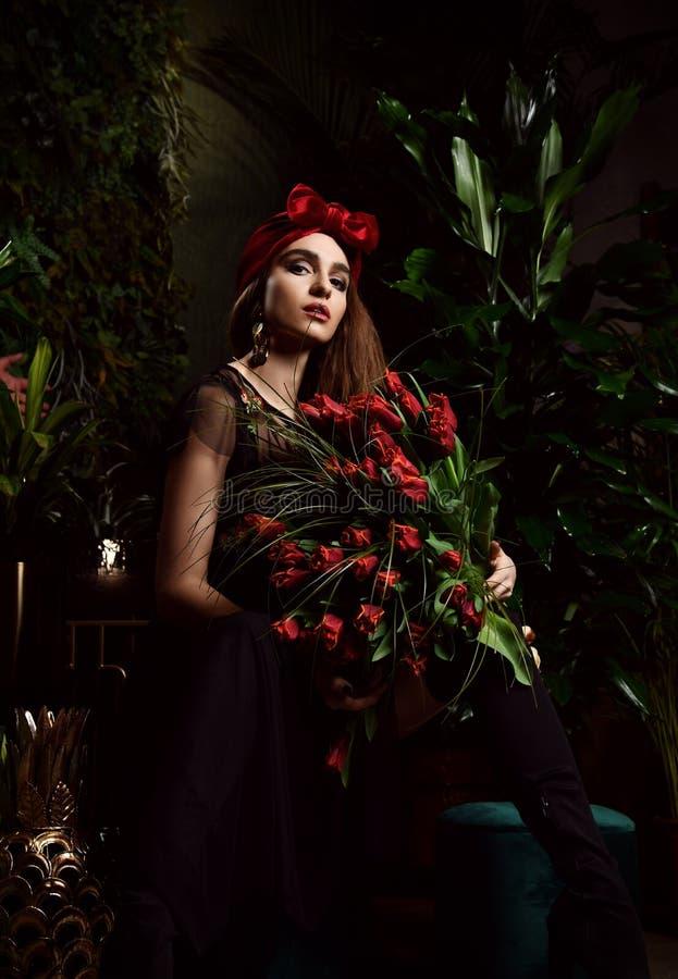 Jeune femme de cru avec le grand bouquet des fleurs rouges de tulipe de ressort frais avec des ampoules Feuilles de vert de style photos libres de droits