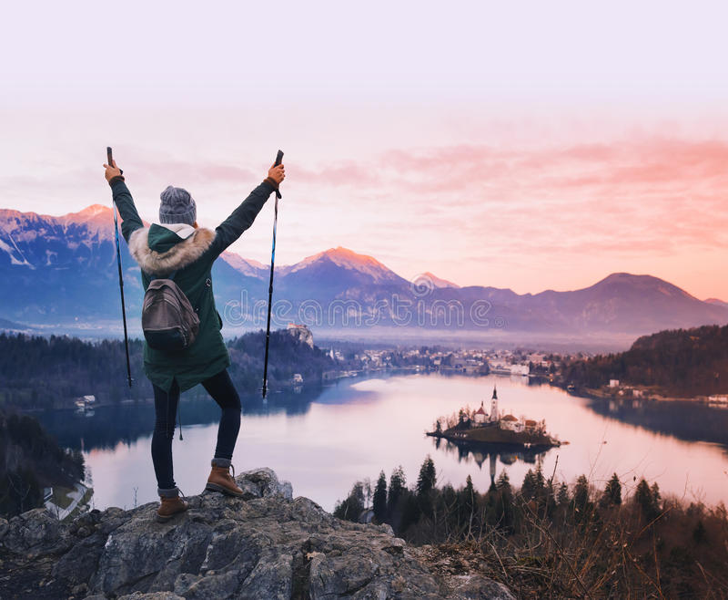 Jeune femme de déplacement regardant sur le coucher du soleil sur le lac Bled, Slovénie, images stock