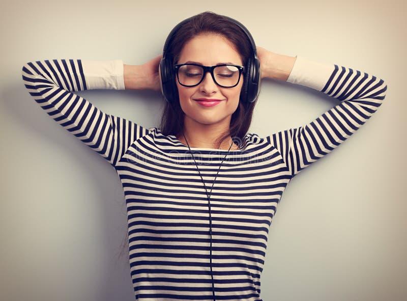 Jeune femme de détente heureuse dans des écouteurs écoutant le musi calme photo libre de droits