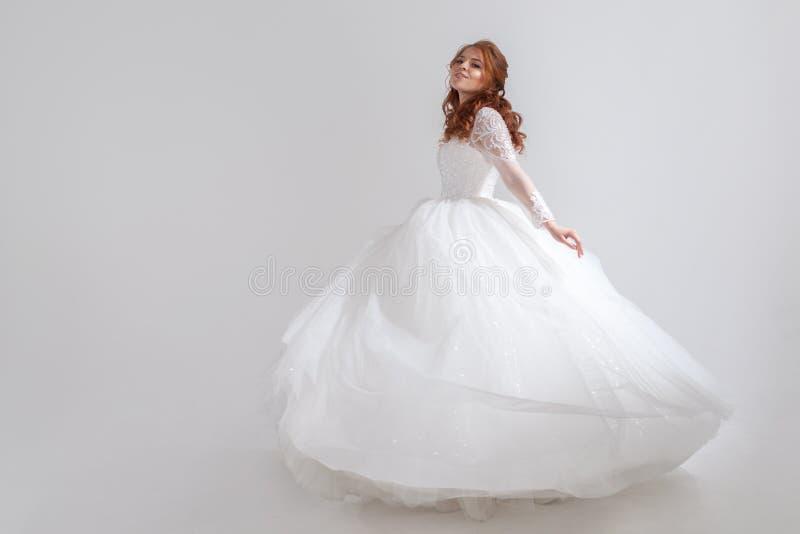 Jeune femme de danse dans la robe de mariage Jeune mariée avec du charme sur le fond clair photographie stock libre de droits