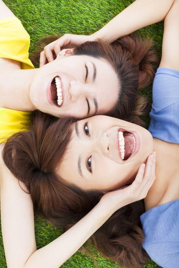 Jeune femme de deux plaisirs se trouvant sur l'herbe photo stock