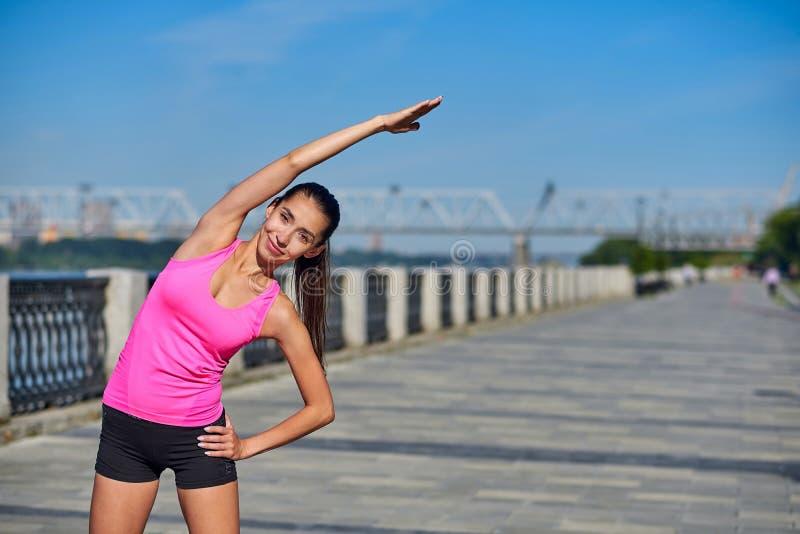 Jeune femme de forme physique étirant des mains après course dehors apr?s course image libre de droits