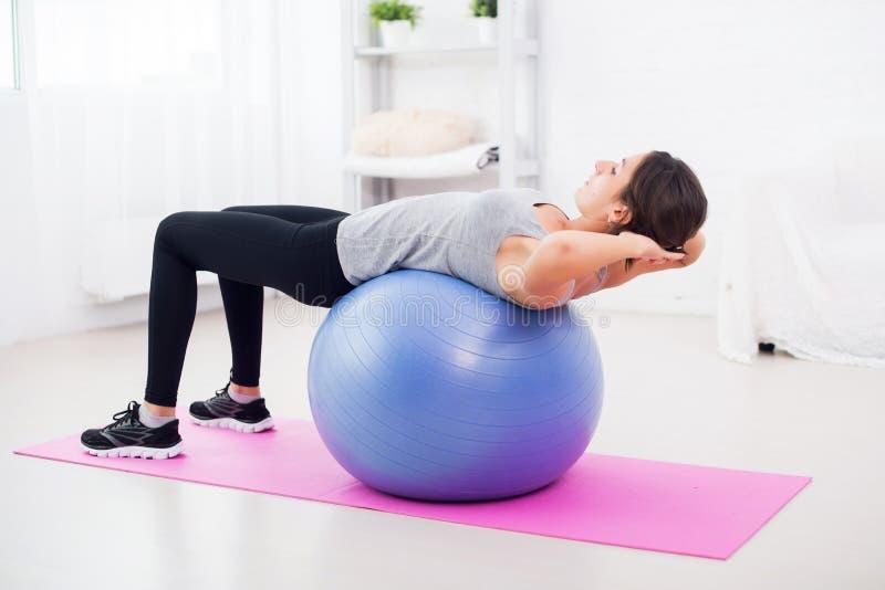 Jeune femme de forme physique faisant des craquements abdominaux dessus photos stock