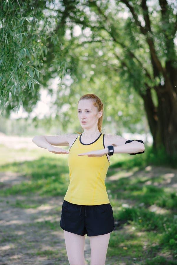 Jeune femme de forme physique faisant l'exercice avant course photo stock