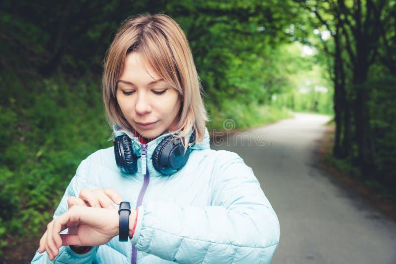 Jeune femme de forme physique de portrait regardant sa montre intelligente tout en faisant une pause de la formation de sports Vé image libre de droits