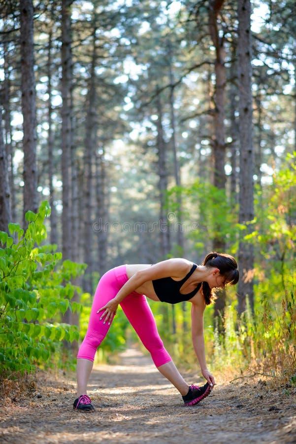 Jeune femme de forme physique s'étirant dans le pin Forest Female Runner Doing Stretches Concept sain de style de vie image stock