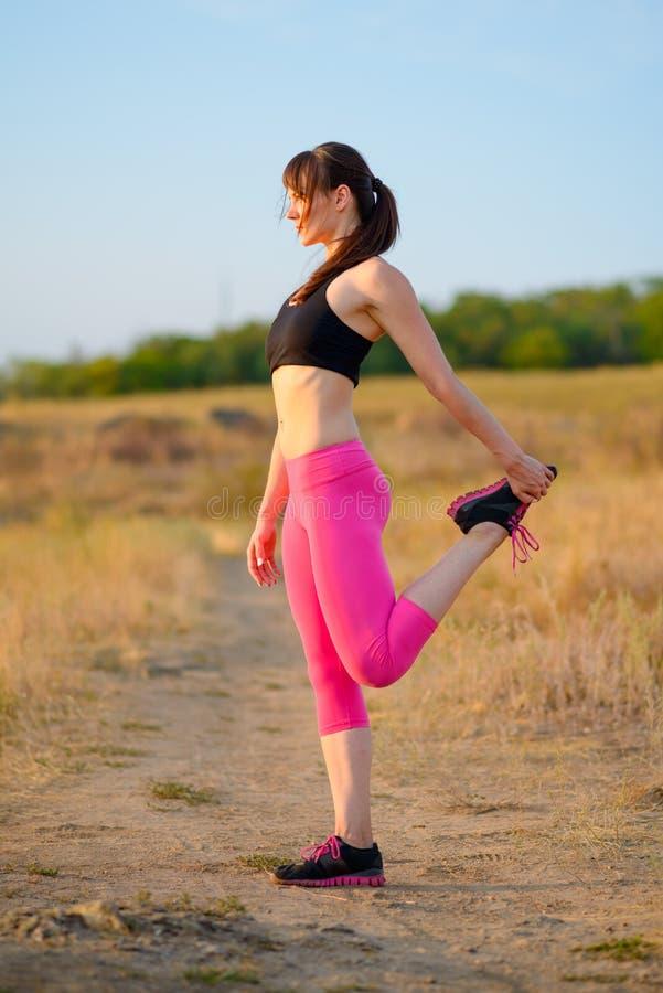 Jeune femme de forme physique s'étirant en parc sauvage Coureur femelle faisant des bouts droits Concept sain de style de vie images stock