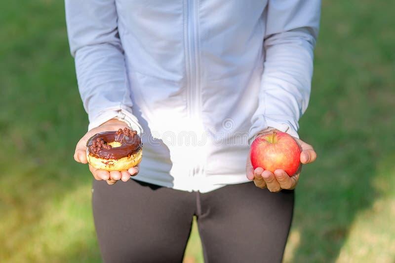 Jeune femme de forme physique se tenant dans des mains pomme et beignet rouges photographie stock libre de droits