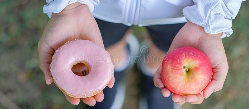 Jeune femme de forme physique se tenant dans des mains pomme et beignet rouges photographie stock