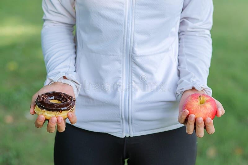 Jeune femme de forme physique se tenant dans des mains pomme et beignet rouges images stock